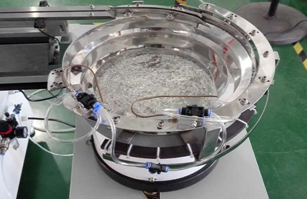 Vibrating bowl feeds components automatically.